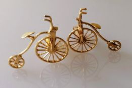 An artisan gold pair of cuff links in the form of penny farthings, unmarked, testing for 18ct, 9.8g