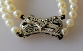 An Art Deco-style two-row necklet of ninety-eight/one hundred and eight graduated cultured pearls