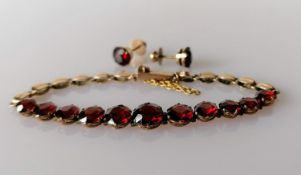 A garnet and gold bracelet with matching earrings, unmarked, the eleven garnets range from 0.5-1.0