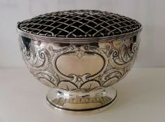 A late Victorian silver punch bowl or table centre with embossed rococo decoration on a spreading