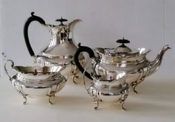 A George V four-piece matching silver tea service of oval bombe form, ebonized fruitwood handles,