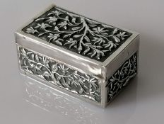 An early 20th century Chinese oblong silver snuff box decorated in relief with prunus blossoms by