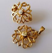 A gold filigree brooch, 20mm diam. and matching pendant, 17mm diam. set with diamond decoration,