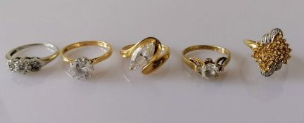 A three-cluster graduated diamond ring in a white gold claw setting; three gem-set yellow gold dress