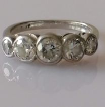 A five-stone graduated diamond platinum ring in a rubbed-over setting, largest stone approximately