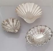 A Victorian larger silver scallop shell, another smaller with husks in relief, both on three ball