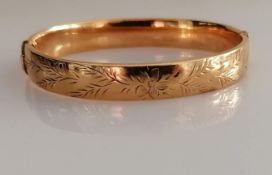 A 9ct yellow gold bangle with etched decoration, 62mm x 58mm, hallmarked for Birmingham, 1970, clasp