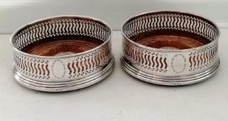 A pair of silver bottle coasters with pierced decoration, vacant cartouches, on stepped bases by W I