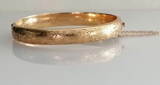 A mid-century 9ct yellow gold bangle with etched decoration, inscription to inside, import marks,