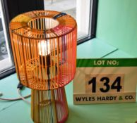 An Orange/Yellow/Brown/Red Table Lamp formed of Plastic Cord Over a Steel Frame